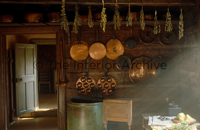 Dried herbs hang from the beam in the kitchen which has a selection of copper pans and griddles on the walls