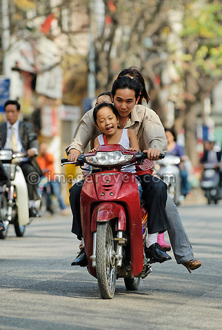 Asia, Vietnam, Hanoi. Hanoi old quarter. Vietnamese family riding on a small motorbike through Hanoi.