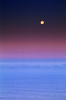 Full moon setting at dawn in purple sky over the Pacific Ocean along the Big Sur Coast, Monterey County, California.