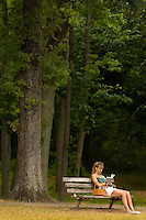 A woman reads a book on a bench at Freedom Park in the Myers Park neighborhood in Charlotte, NC. Myers Park is one of the premier neighborhoods in North America and known for its large canopy of trees.