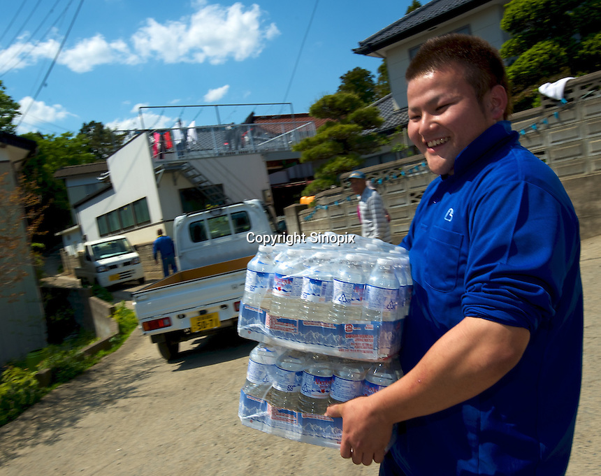 Water from OGA for Aid is distributed on top of a hill at Ishihama where they have no water or electricity and little food just outside Minamisanriku, Myiagi, Japan.The fishing port of Minamisanriku, Miyagi, Japan was devastated by the tsunami where the popultion was reduced from 18,000 to about 8,000