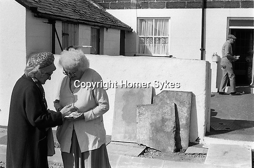 """Dunting the Freeholder. Freeholders outside the """"Freeholders of Newbiggin-by-the-Sea, Northumberland. Householders who's homes back onto the moor pay a 'way leave' of 20 pence  per year in exchange for a handful of nuts. Freeholder handing over the nuts. 1974"""