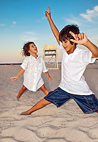 Kids dancing on the beach.