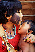 A-Ukre village, Xingu, Brazil. Young Kayapo mother with her baby; intricate black face paint design.