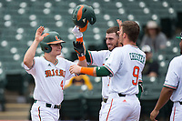 Michael Burns (44) of the Miami Hurricanes is congratulated by his teammates after hitting a solo home run against the Georgia Tech Yellow Jackets during Game One of the 2017 ACC Baseball Championship at Louisville Slugger Field on May 23, 2017 in Louisville, Kentucky.  The Hurricanes walked-off the Yellow Jackets 6-5 in 13 innings. (Brian Westerholt/Four Seam Images)