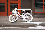 Bicycle covered with snow and ice after a spring snow in Missoula, Montana