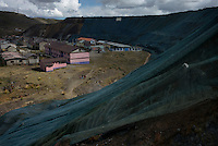 Toxic mine tailings are seen surrounding  the Chamapamarca neighborhood of Cerro de Pasco, Peru. Green mesh has been placed over the portion of the tailings pile closest to homes.