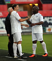 Adrian Forbes of Swansea (R) is greeted by James Thomas during the Alan Tate Testimonial Match, Swansea City Legends v Manchester United Legends at the Liberty Stadium, Swansea, Wales, UK