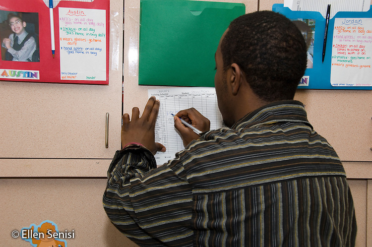 MR / Albany, NY.Langan School at Center for Disability Services (private nonprofit disability services).Upper elementary classroom/Day Program.Teaching assistant (African-American) writes on student's toileting chart on wall. Staff documents events and anecdotes about students throughout the day. Toileting is an issue for many people with CP because many do not have the required muscle control to take care of their bathroom needs independently..MR: Wes2.© Ellen B. Senisi