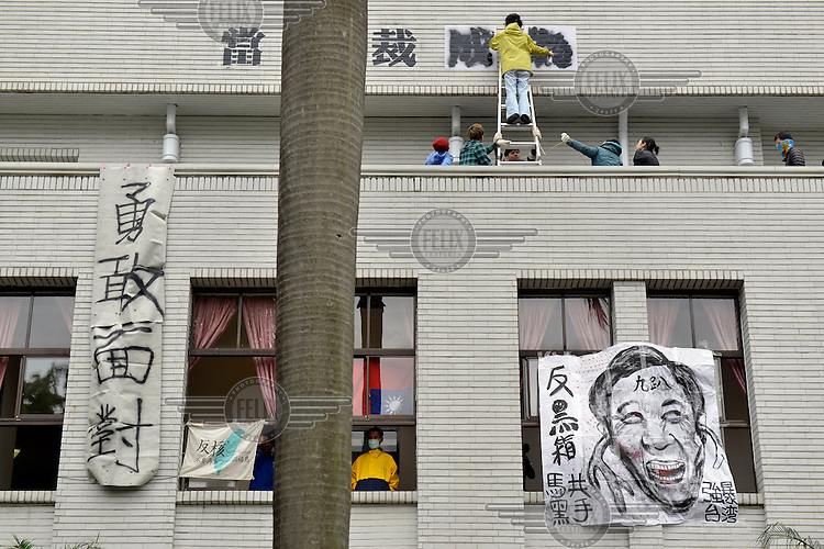 """Protestors stencil a sign onto the wall of Taiwan's Legislative Yuan (Parliament) building on the 4th day of its occupation by students opposed to the passing of the Cross-Straight Service and Trade Agreement between Taiwan China. The sign reads: 'When dictatorship becomes reality, revolution becomes our duty.' A caricature of Taiwan's President Ma ying-joeh hangs in the window.  The students, and many normal Taiwanese, fear the erosion of their hard-won democracy and, eventually, independence, making them, in the words of one student protestor 'no better off than Hong Kong'. Ma ying-jeoh bears the brunt of the protestors ire; known as """"Ma 9%"""" after his latest approval rating, he is seen as kowtowing to the demands of China and selling out Taiwan."""