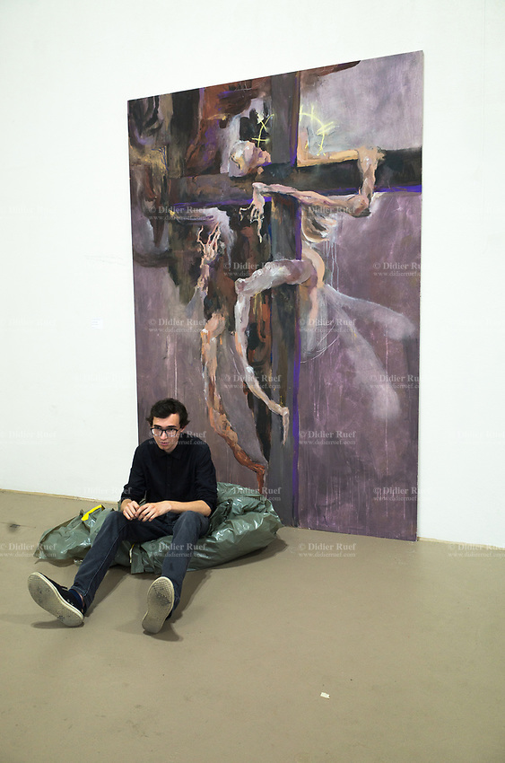 """Switzerland. Canton Ticino. Lugano. Opening of CSIA students' exhibition at the Ex Macello. The student Daniel Drabek sits on the ground on a plastic sheet near his painting, called """"Dipinto inrisolto"""". Daniel Drabek is a student from the Maturità professionala (2016-2017) at Centro scolastico per le industrie artistiche (CSIA). 3.06.2017 © 2017 Didier Ruef"""