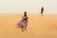 An Arab Moor girl who lives in the Sahara Desert town of Boujbeja runs in the sand smiling. /Felix Features