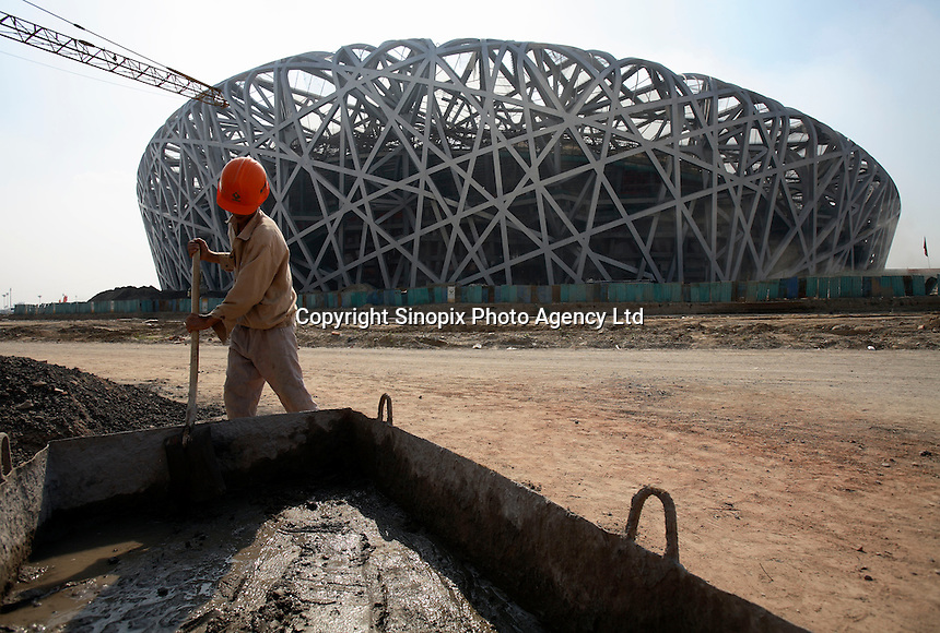 """A construction worker mixes cement in front of the National Stadium, AKA """"The Bird's Nest"""" in Beijing, China..04 Sep 2007"""