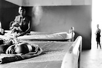 Uganda. West Nile. Adjumani. Hospital.  NGO (non governmental organisation) MSF Switzerland ( Médecins Sans Frontières. Doctors without Borders) works in the hospital. A young ill boy suffers from severe cerebral malaria lies on the bed. Seated on another bed, a mother holds her sick child in her arms. A young boy stands on the ward's door. West Nile Province and West Nile District) is a region in north-western Uganda. © 1989 Didier Ruef