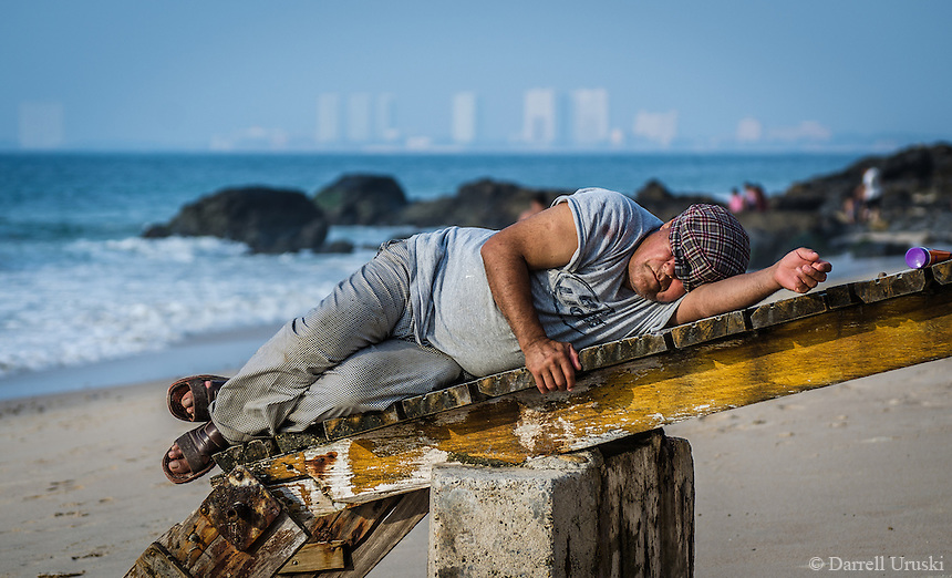 Urban Street, Beach Scene. Sleepy day on a Mexican beach, Photographic Art of A Mexican Man catching some sleep in the hot Mexican Sun as the waves crash in on the beach.