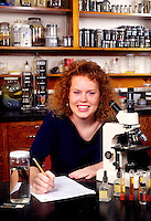 Student girl in 11th grade in high school science class experiments with microscope in schoo