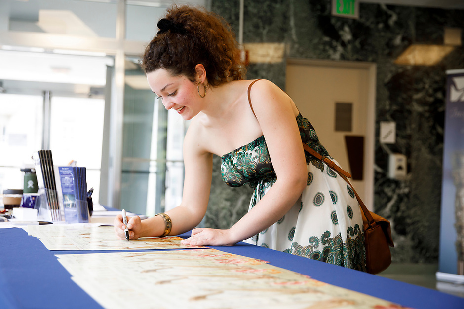 Myriam Blardone of Canada signs posters at contestant registration during the 11th USA International Harp Competition at Indiana University in Bloomington, Indiana on Tuesday, July 2, 2019. (Photo by James Brosher)
