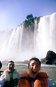 Iguassu Falls, Brazil. Exhilarated tourists in an inflatable boat wet from being under the falls.