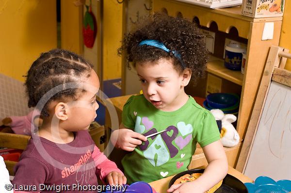 Education Preschool 3-4 year olds two children talking in kitchen pretend play area horizontal