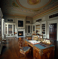 An ornate hand-painted stucco ceiling in this neo-classical library at Osterley Park, which is furnished with inlaid desks and pedimented bookcases