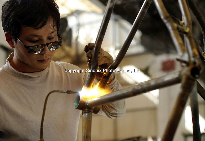 A worker welds together bicycle frames at the Shanghai Forever Bicycle Factory (SFBF) in Shanghai, China. Despite the government's efforts to encourage automobile ownership in recent years, the bicycle remains the most popular mode of transportation for China's masses. The SFBF, it's products once a must have and a symbol of status for every Chinese family, are now supplying bicycles to countries around the world. It has seen it's sales increase 59% percent in the past year to 876 million yuan (euro 89.36 million)..21-APR-04