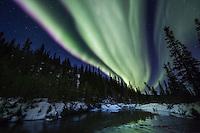 Nothern lights reflect in a stream in the Alaska Range mountains, interior, Alaska.