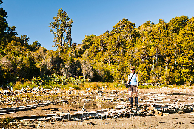 Female tramper poses on driftwood ladden shore of Saltwater Lagoon at low tide - Westland National Park, West Coast, New Zealand