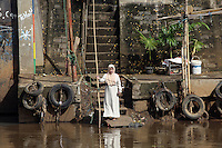 An Indonesian woman waits for a boat on the banks of the Ciliwung River, a waterway that has been described as one of the most polluted rivers in the world. The river often floods, breaking its banks sending its polluted water into the nearby communities.