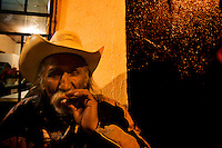 """A member of a """"Trio band"""" smoking tobacco cowboy style. <br /> <br /> In northern mexico bands known as """"trios"""" are well known for their services, private playings. In restaurants, bars or in the street is often see them offering songs, from traditional mexican music like mariachis, banda, corridos to classic rock."""