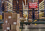 Interior large warehouse with freight in motion on a conveyor belt.