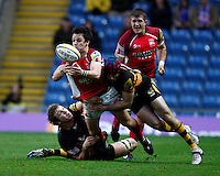 Photo: Richard Lane/Richard Lane Photography. London Welsh v London Wasps. 29/12/2012. Welsh's Rob Lewis is tackled by Wasps' Joe Launchbury and Chris Bell.