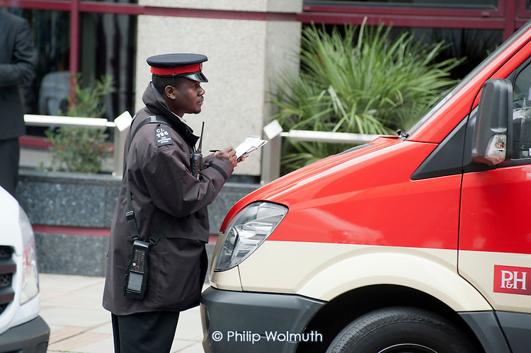 A traffic warden issues a Penalty Notice in Gresham Street, City of London.