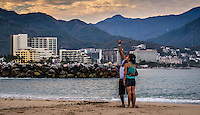 Urban Street Photograph of a coupe taking a self portrait of themselves on the beaches of Puerto Vallarta, Mexico.