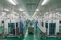 CHINA. Workers monitor solar cell production at Yingli Solar Company in Baoding City. 2011