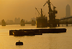 River Thames Flood Barrier Canary Wharf Canada Square building London UK 1990s 1991 Cranes loading ship working on river Thames barges