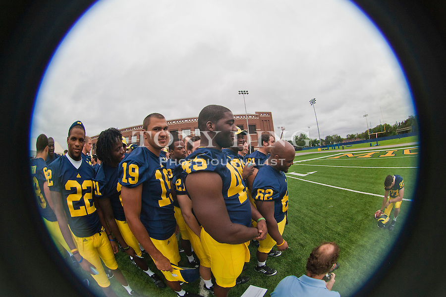 Michigan wide receiver Darryl Stonum (22), safety Zac Johnson (19), and linebacker Obi Ezeh (45) wait with teammates for their picture to be taken at the annual NCAA college football media day, Sunday, Aug. 22, 2010, in Ann Arbor, Mich. (AP Photo/Tony Ding)