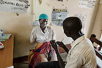 """N. Uganda, Gulu District. Joshua Tugumisirize, a visiting PCAF psychiatrist & Freddy Odong, a PCAF nurse, perform a psychiatric assessment and counseling at the local rural clinic in Gulu. """"Ruth"""" lost her arm during the war and struggles with depression. She has no husband but a young son helps her. """"Ruth"""" walks many miles to come to the rural clinic where she gets periodic counseling & treatment. It took nearly an hour just to drive to her home."""