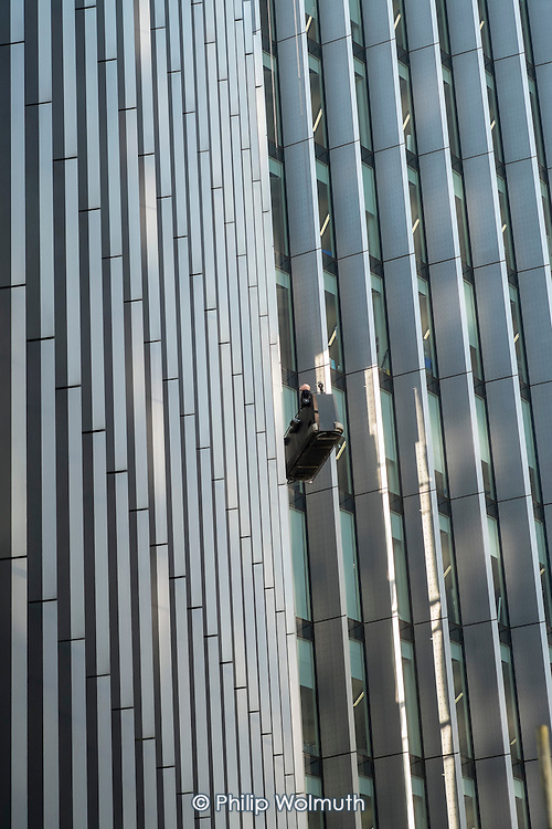 A maintenance worker checking windows from a cradle on a high-rise office block in the City of London.