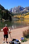 Caucasian male artist painting the Maroon Bells Peaks, near Aspen, Colorado, USA