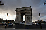 Several lamp posts are seen in the foreground looking back to a view of the Arch De Triumph in Paris france.  Traffic moves through the Place Charles De Gaulle past the Arch.