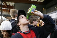 Switzerland. Canton Bern. Bern. A young man drinks a bottle of beer. He is a fan of the SCB Bern hockey club. He stands outside of the Bern Arena and waits for the doors to open. © 2006 Didier Ruef