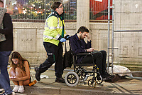 Pictured: A man is taken a way in a wheelchair by a St John Ambulance member of staff in Wind Street, Swansea. Monday 31 December 2018 and Tuesday 01 January 2019<br /> Re: New Year revellers in Wind Street, Swansea, Wales, UK