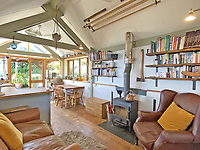 BNPS.co.uk (01202) 558833. <br /> Pic: LillicrapChilcott/BNPS<br /> <br /> Pictured: Living space with log burner.  <br /> <br /> A pretty wooden cottage with spectacular panoramic sea views is on the market for £595,000.<br /> <br /> The aptly-named The Hut is an eco-built property set on a hill in the hugely sought-after Cornish village of Mousehole.<br /> <br /> The small but perfectly-formed home looks down over Mousehole harbour and across Mounts Bay to St Michael's Mount.