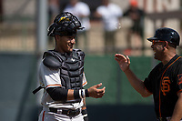 San Francisco Giants catcher Ricardo Genoves (6) laughs with a coach between innings of a Minor League Spring Training game against the Cleveland Indians at the San Francisco Giants Training Complex on March 14, 2018 in Scottsdale, Arizona. (Zachary Lucy/Four Seam Images)