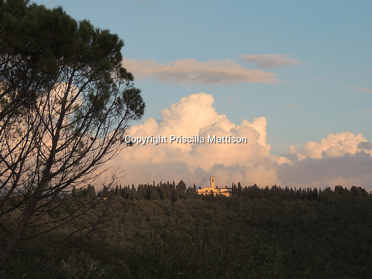 Billowing clouds surround a distant church in Tuscany.
