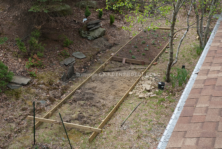 Raised beds being made in a new shade garden under trees in woodland setting for new landscaping, view from house rooftop