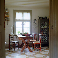 The wooden floors of this Swedish country kitchen have been painted with a simple geometric pattern