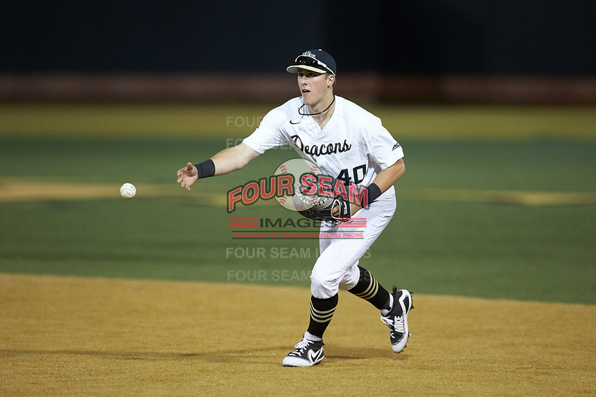 Cole McNamee (40) of the Wake Forest Demon Deacons flips the ball towards first base during the game against the North Carolina State Wolfpack at David F. Couch Ballpark on April 18, 2019 in  Winston-Salem, North Carolina. The Demon Deacons defeated the Wolfpack 7-3. (Brian Westerholt/Four Seam Images)