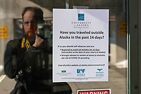 Photographer's self portrait with information posted about prevention measures at UAA in response to the spread of COVID-19.