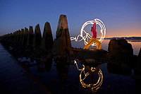 Woman practising yoga by the sea at Crammond Causeway, Edinburgh, Scotland, UK